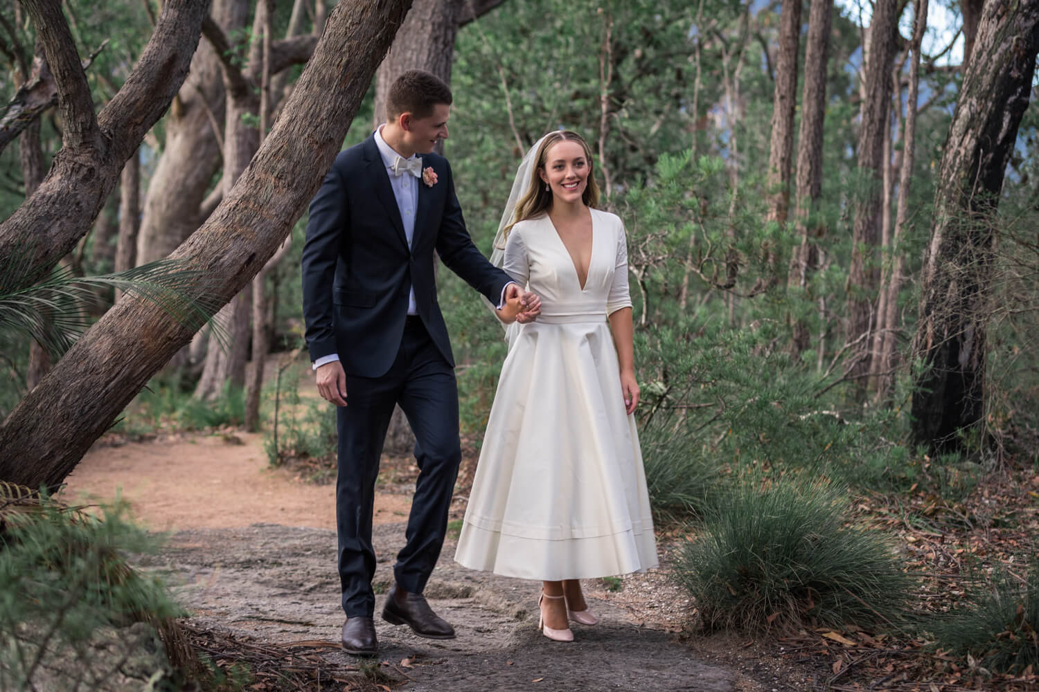 bride and groom holding hands in the forest - wedding photography styles